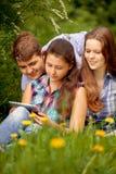 Adolescentes en el parque. bookr u ordenador. Concepto Foto de archivo libre de regalías