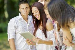Adolescentes en el parque con la tableta Foto de archivo libre de regalías