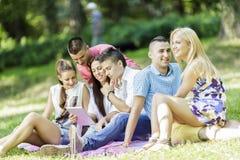 Adolescentes en el parque con la tableta Fotos de archivo libres de regalías
