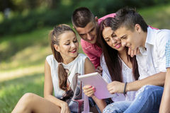 Adolescentes en el parque con la tableta Fotografía de archivo libre de regalías