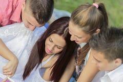 Adolescentes en el parque con la tableta Imágenes de archivo libres de regalías