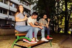 Adolescentes en el parque que se sienta en un banco de madera Fotos de archivo libres de regalías