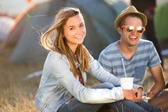 Adolescentes en festival de música del verano, la reclinación, la consumición y la consumición Fotos de archivo