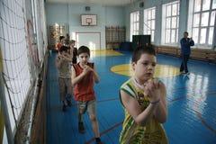 Adolescentes en la escuela en clase de la gimnasia Imágenes de archivo libres de regalías