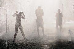 Adolescentes en la fuente en el día de verano caliente Foto de archivo libre de regalías