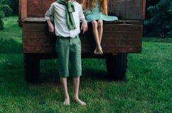 Adolescentes en la granja, niños del ` s del granjero en el verano cosechando y descanse a una muchacha descalza en un vestido ve Fotos de archivo