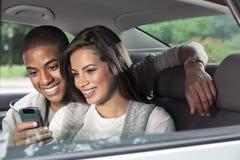 Adolescentes en la parte de atrás del coche con el teléfono móvil Foto de archivo