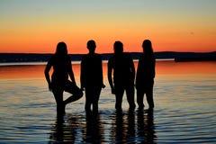 Adolescentes en la puesta del sol como siluetas en el lago Imagen de archivo