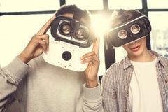 Adolescentes en las auriculares de la realidad virtual que se unen y que miran la cámara, adolescentes que tienen concepto de la  Fotos de archivo libres de regalías