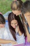 Adolescentes en parque con la tableta Imagenes de archivo