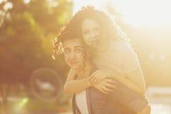 Adolescentes en parque en la puesta del sol Imagenes de archivo