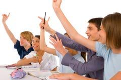 Adolescentes en sala de clase con los brazos para arriba Fotografía de archivo
