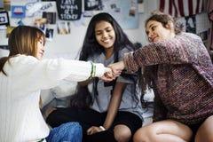 Adolescentes en un concepto de la amistad del puño del dormitorio que topa Imagenes de archivo