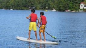 Adolescentes en un soporte encima del tablero de paleta en un lago Imágenes de archivo libres de regalías