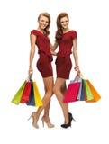 Adolescentes en vestidos rojos con los panieres Foto de archivo libre de regalías