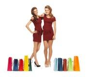 Adolescentes en vestidos rojos con los panieres Imágenes de archivo libres de regalías