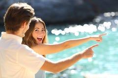 Adolescentes entusiasmados que apontam a praia em férias fotos de stock