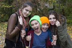Adolescentes et deux garçons sur le terrain de jeu photos stock