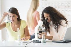 Adolescentes expérimentant dans la classe de chimie Image stock