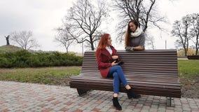 Adolescentes fêmeas que escutam a música no smartphone que senta-se no banco video estoque
