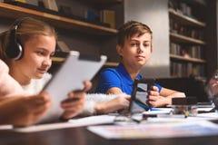 Adolescentes fascinados que usan sus artilugios Imágenes de archivo libres de regalías