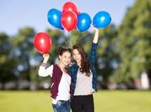 Adolescentes felices con los globos del helio Fotos de archivo