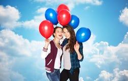 Adolescentes felices con los globos del helio sobre el cielo Imagen de archivo