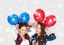 Adolescentes felices con los globos del helio sobre nieve Fotos de archivo