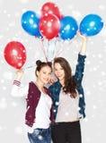 Adolescentes felices con los globos del helio sobre nieve Fotografía de archivo libre de regalías