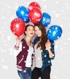 Adolescentes felices con los globos del helio sobre nieve Foto de archivo libre de regalías