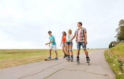 Adolescentes felices con rollerblades y longboards Foto de archivo