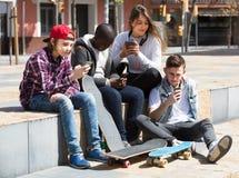 Adolescentes felices con smartphones en día de primavera Imagen de archivo