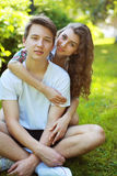 Adolescentes felices de los pares del retrato que se sientan en la hierba en verano Imagen de archivo