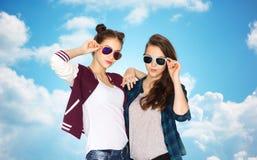 Adolescentes felices en gafas de sol sobre el cielo azul Foto de archivo