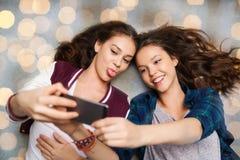 Adolescentes felices en piso y selfie el tomar Imágenes de archivo libres de regalías