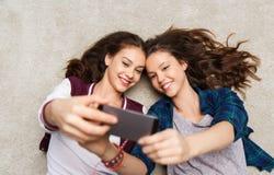 Adolescentes felices en piso y selfie el tomar Imagen de archivo