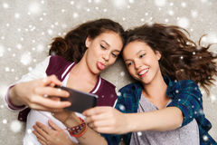 Adolescentes felices en piso y selfie el tomar Fotografía de archivo libre de regalías