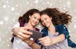 Adolescentes felices en piso y selfie el tomar Foto de archivo