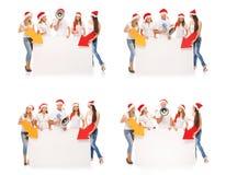 Adolescentes felices en sombreros de la Navidad con las banderas blancas Foto de archivo libre de regalías