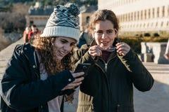 Adolescentes felices encendido de ellos en el sombrero de punto que manda un SMS con pho de la célula Imagen de archivo libre de regalías