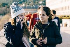 Adolescentes felices encendido de ellos en el sombrero de punto que manda un SMS con pho de la célula Foto de archivo libre de regalías