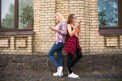 Adolescentes felices jovenes del inconformista que se divierten en parque del verano Imagen de archivo
