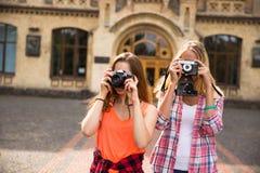 Adolescentes felices jovenes del inconformista que toman imágenes y que se divierten en parque del verano Foto de archivo libre de regalías