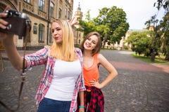 Adolescentes felices jovenes del inconformista que toman imágenes y que se divierten en parque del verano Imagen de archivo