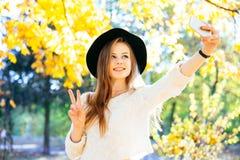 Adolescentes felices jovenes que hacen el selfie y que se divierten en parque del otoño Imagenes de archivo