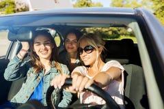 Adolescentes felices o mujeres jovenes que conducen en coche Fotos de archivo libres de regalías