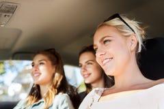 Adolescentes felices o mujeres jovenes que conducen en coche Imagen de archivo libre de regalías