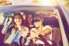 Adolescentes felices o mujeres jovenes que conducen en coche Imágenes de archivo libres de regalías
