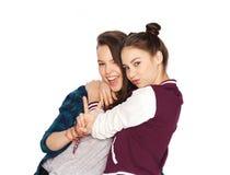 Adolescentes felices que abrazan y que muestran el signo de la paz Imagen de archivo