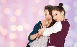 Adolescentes felices que abrazan y que muestran el signo de la paz Imagen de archivo libre de regalías